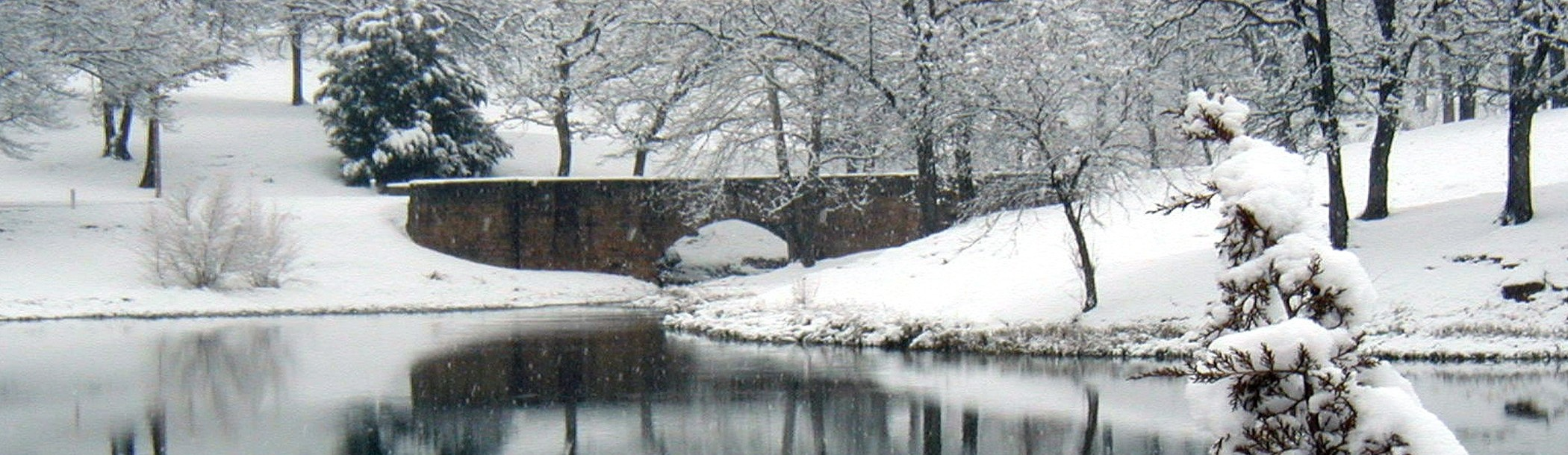 Bridge over a lake with surrounding area covered in snow.